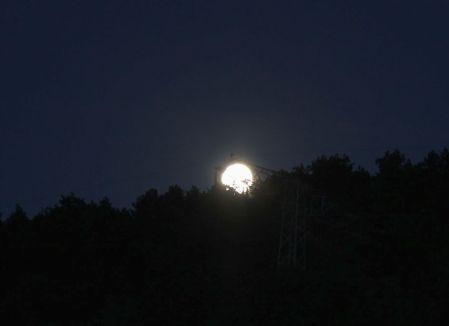Mond beim Versuch sich hinter Hochspannungsmast zu verstecken