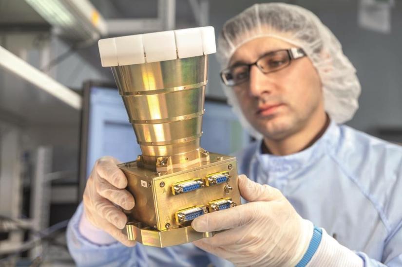 ein Kollege im Reinraum mit einem Sternsensor ASTRO APS in der Hand
