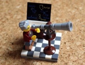 Lego-Männchen schaut durch Fernrohr mit Tafel mit Sternbildern im Hintergrund