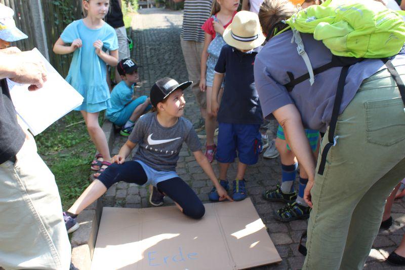 Kinder & Erwachsene diskutieren an der aufgemalten Erde, wo die ISS ungefähr fliegt
